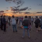 A circle of singers on the beach around a fire as the sun sets