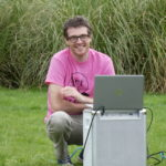 Ross smiling by the laptop and amp