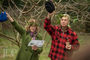Singers in the orchard with ivy crowns and raising hats!